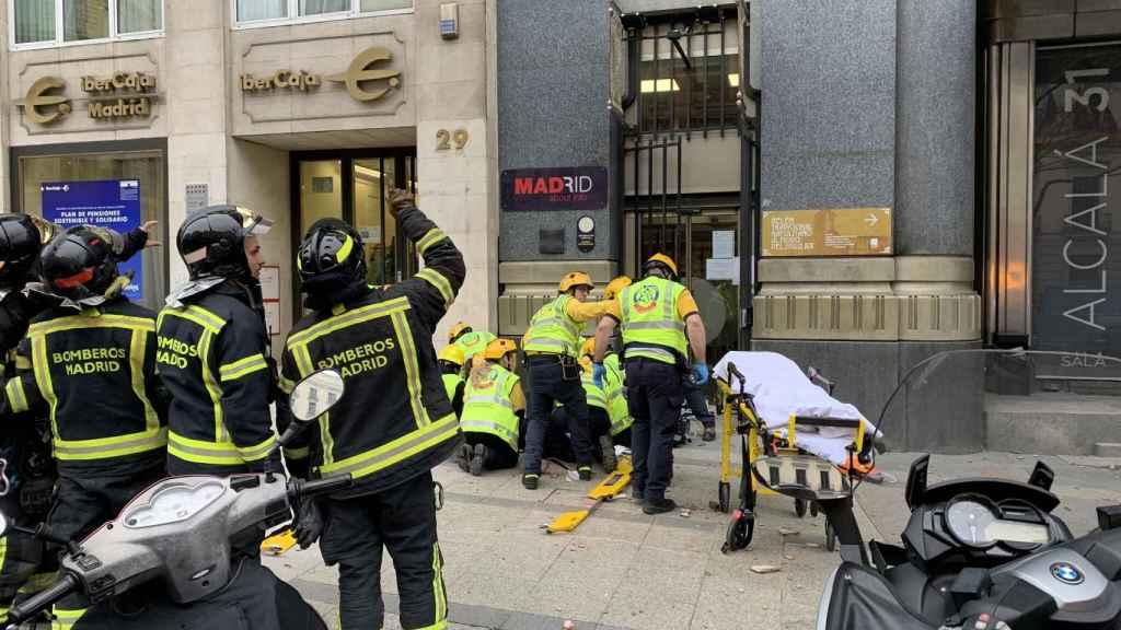 Los bomberos acuden al lugar donde fue golpeada la mujer coreana por un cascote.