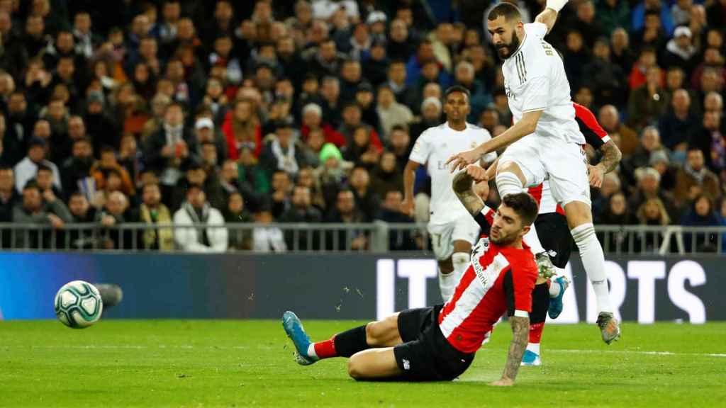 Benzema dispara a puerta con un jugador del Athletic delante