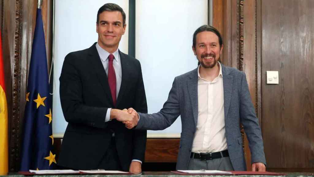 Sánchez e Iglesias estrechan sus manos durante el acto de la firma este lunes 30-D