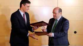 Pedro Sánchez y Andoni Ortuzar intercambian los documentos para la firma del acuerdo entre PSOE y PNV para la investidura.