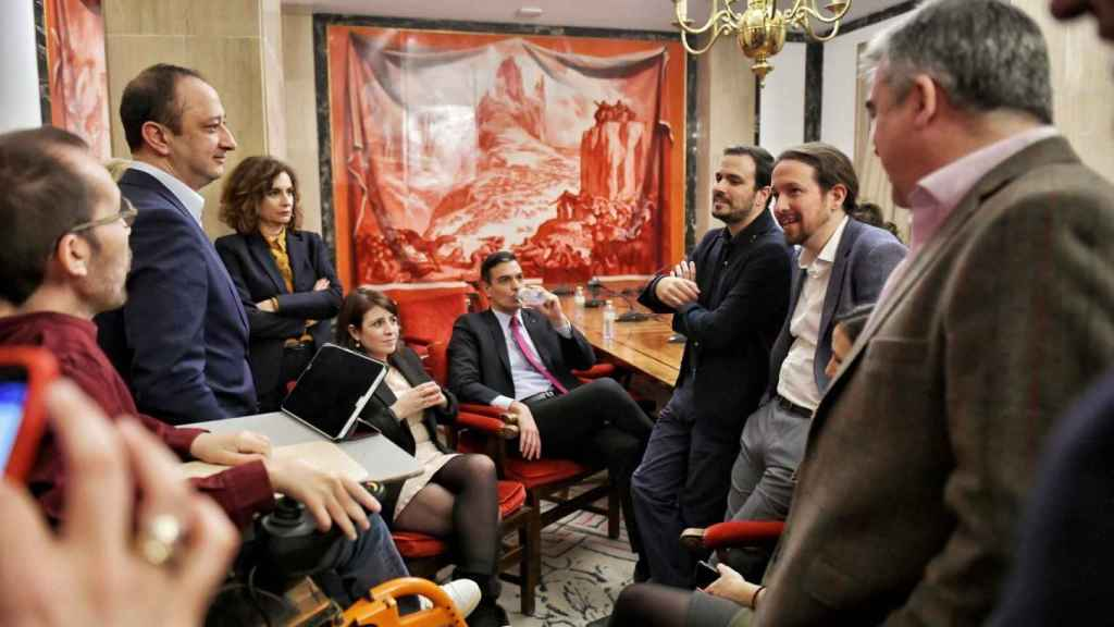 Los líderes del PSOE y UP, Sánchez e Iglesias, charlan con sus equipos tras la presentación del programa de su gobierno.