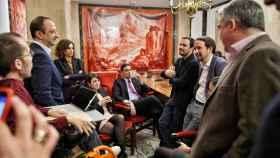 Los líderes del PSOE y Unidas Podemos, Pedro Sánchez y Pablo Iglesias, charlan con sus equipos tras la presentación del programa de su gobierno de coalición.