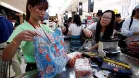 Una mujer haciendo la compra con una bolsa de tela.