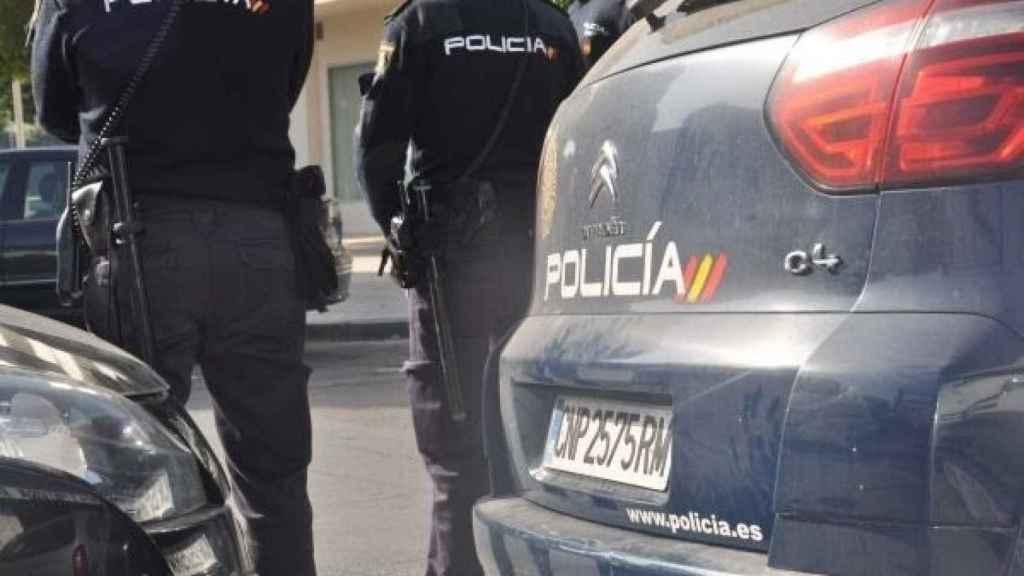 Agentes de la Policía Nacional,  junto a sus coches.