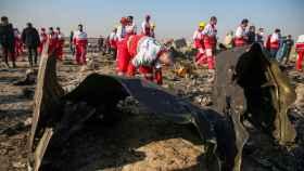 Trabajadores de la Media Luna Roja revisan los escombros del avión.