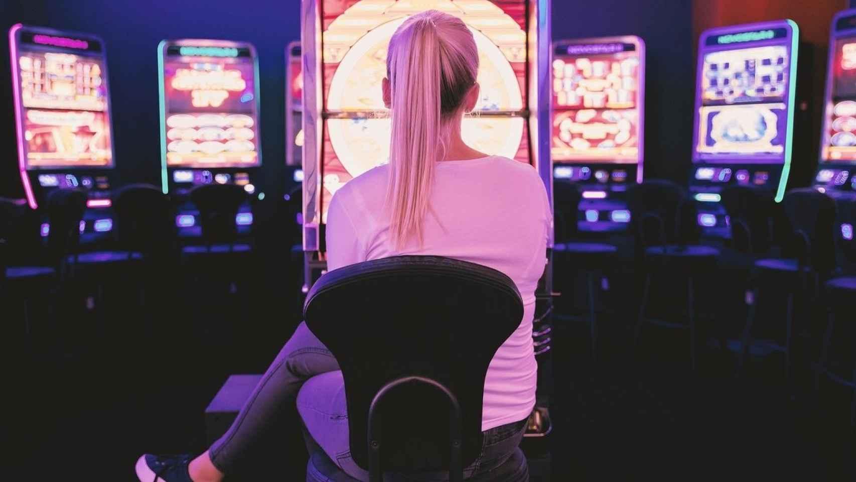 Una mujer en una sala de máquinas tragaperras.