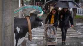 Dos mujeres se protegen de la lluvia. EFE/Julio Muñoz.