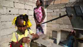 Dos niñas sacan agua de un pozo en Leogane (Haití)