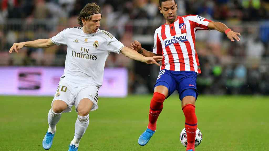 Luka Modric y Renan Lodi pelean por un balón