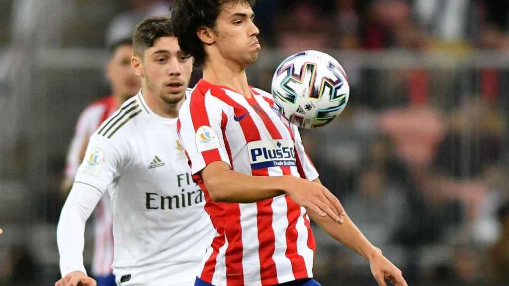 Joao Felix controla el balón con el pecho, presionado por Fede Valverde