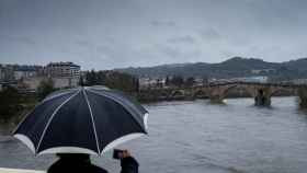 Un hombre fotografía el caudal del río Miño a su paso por Ourense. EFE/Brais Lorenzo.