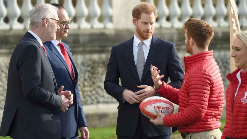 El príncipe Harry habla con un jugador de rugby profesional.