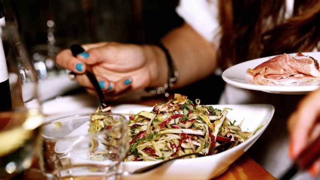 Una mujer degustando un plato de ensalada en un restaurante.