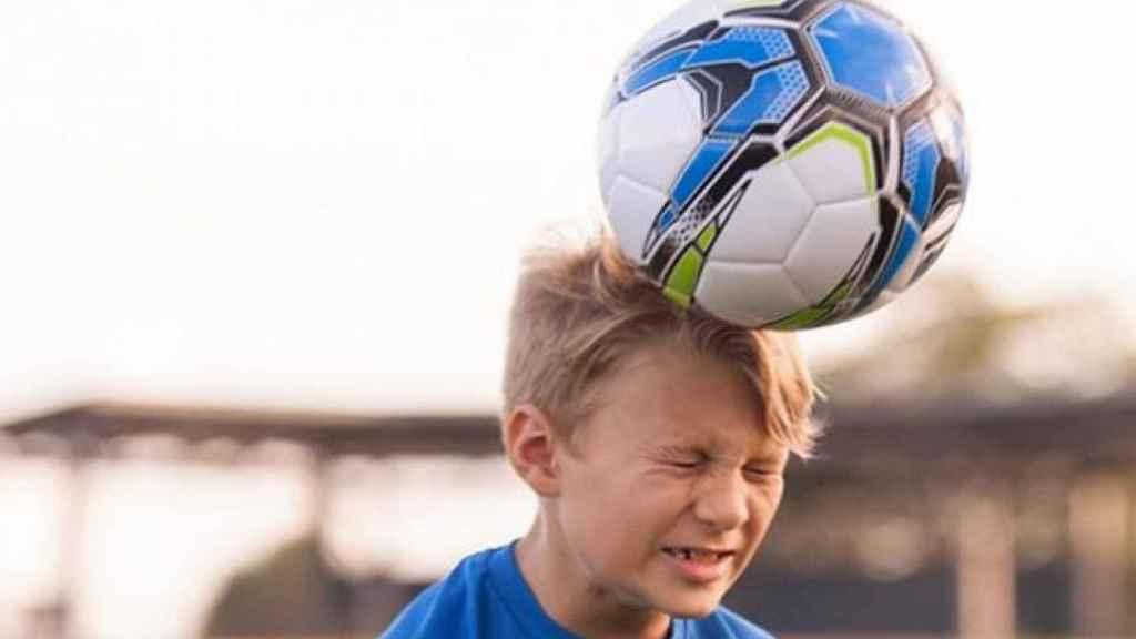Un niño remata de cabeza un balón de fútbol.