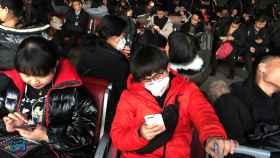Pasajeros con máscara esperan a su avión mientras consultan Internet