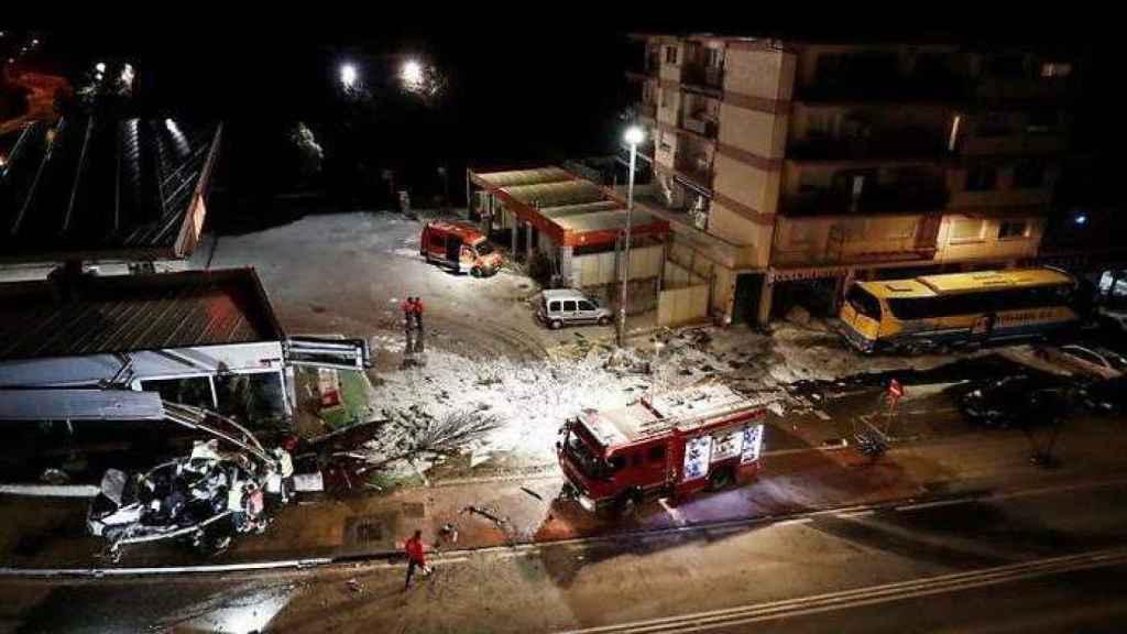 El autobús arrastró el coche accidentado hasta el muro de una gasolinera.