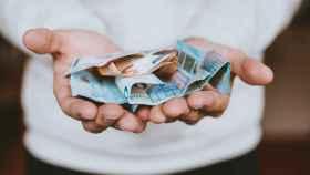 Un hombre sostiene billetes de euro.