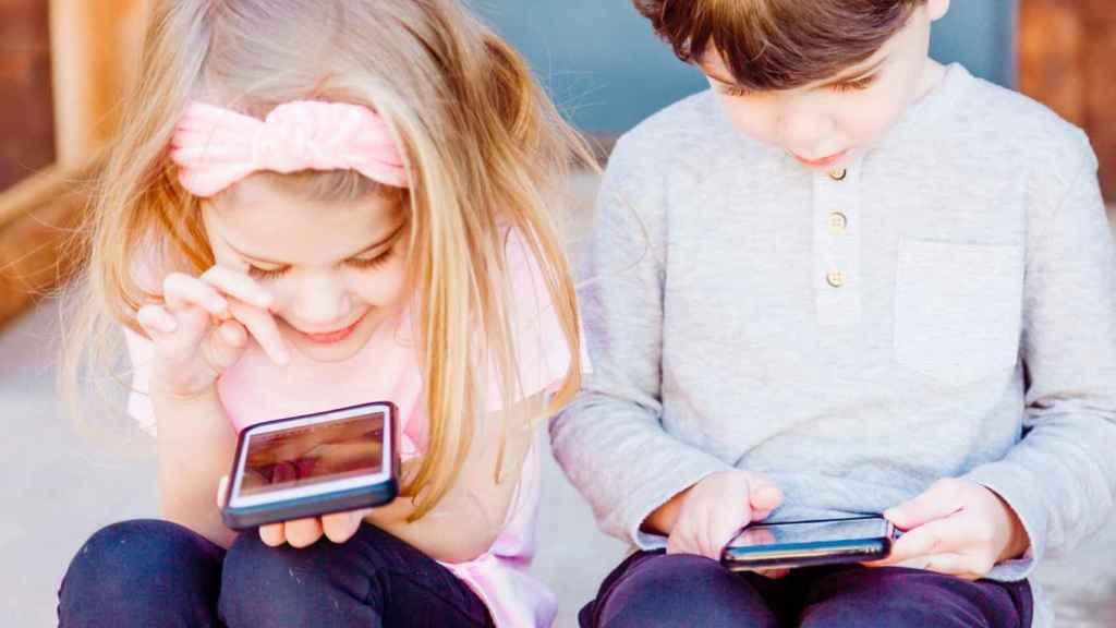 Niños jugando con teléfonos.