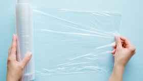 Una mujer desenrollando el papel film de cocina.