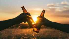Dos amigos brindan con botellines de cerveza.