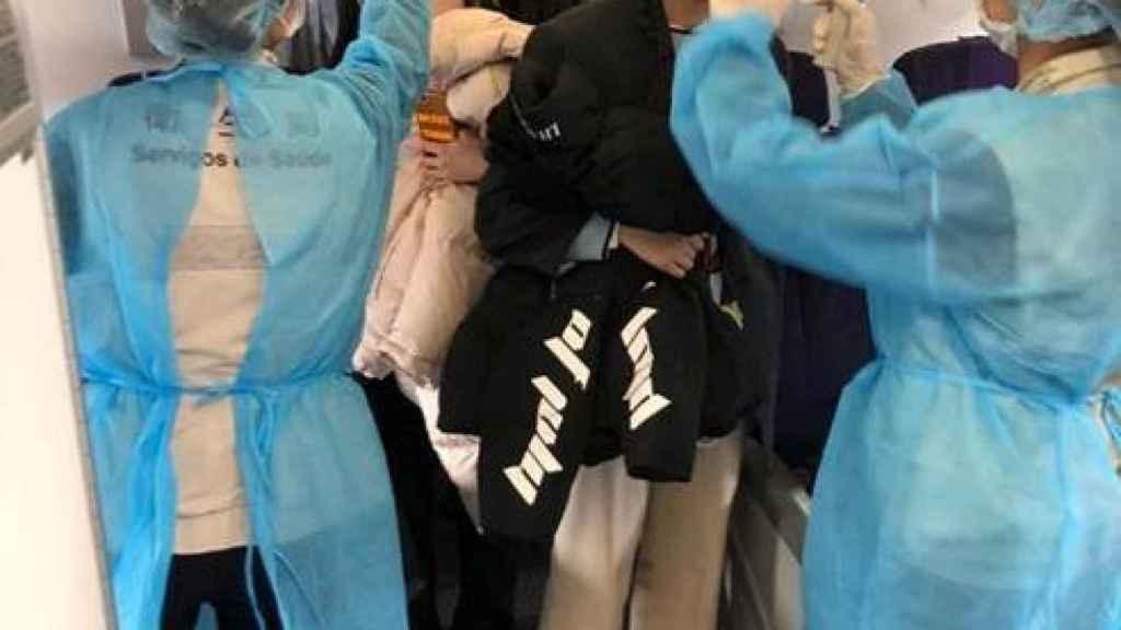 Oficiales miden la temperatura a los pasajeros en un avión de AirChina