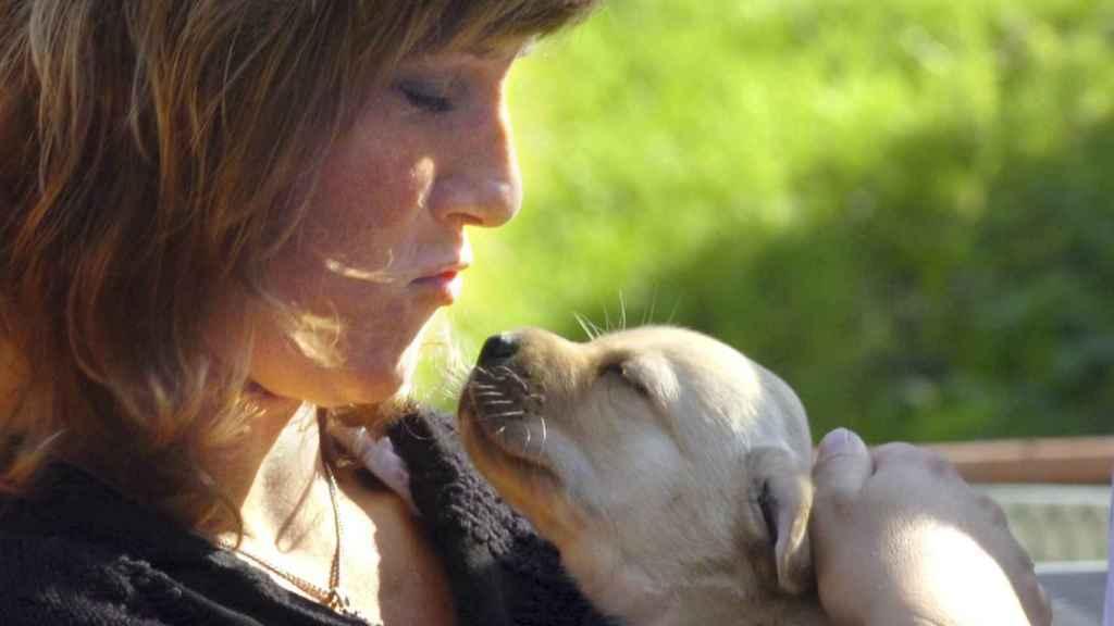 Marta Luisa de Noruega con un cachorro de perro guía en brazos.