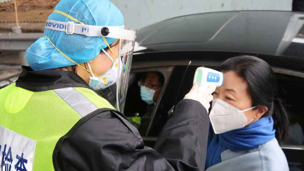 Un guardia de seguridad le toma la temperatura a una señora en Xianning (China), para comprobar que no tiene fiebre.