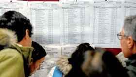 Un grupo de graduados en medicina consulta en las listas el lugar donde realizarán el MIR.
