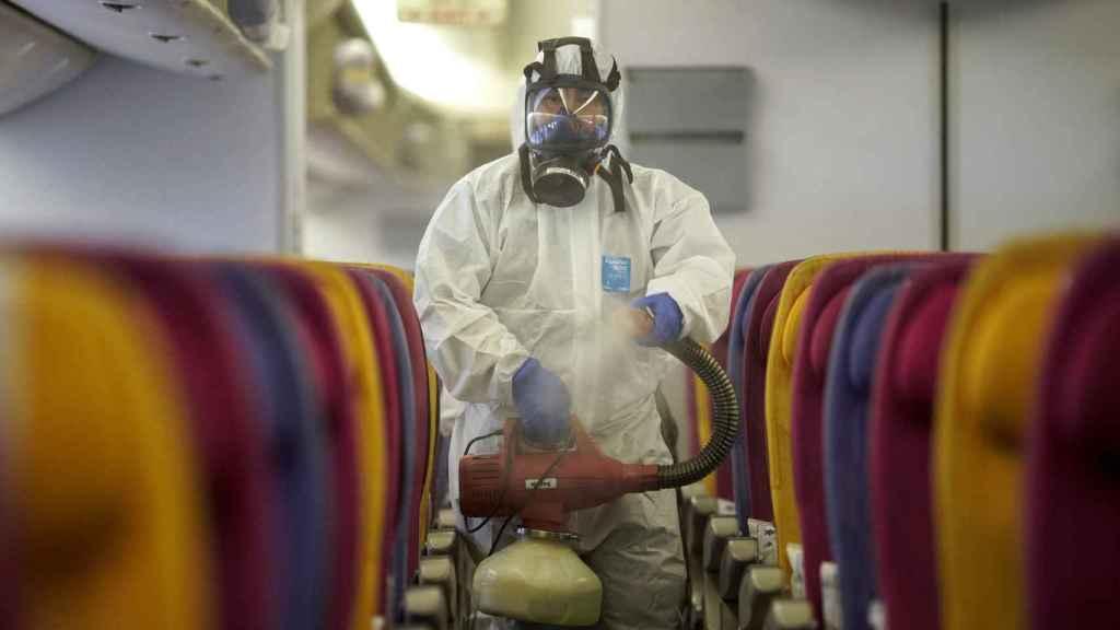 Un miembro de Thai Airways desinfecta un avión procedente de China.