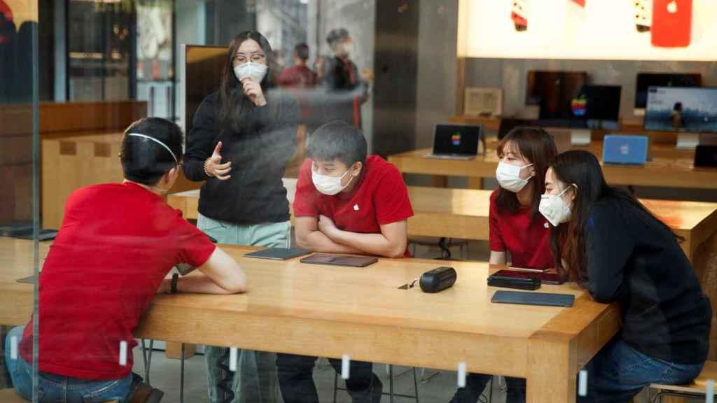 Jóvenes con mascarillas en una Apple Store en Beijing.