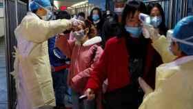 Personal médico toma la temperatura a pasajeros en una estación de tren en enero de 2020 en China.
