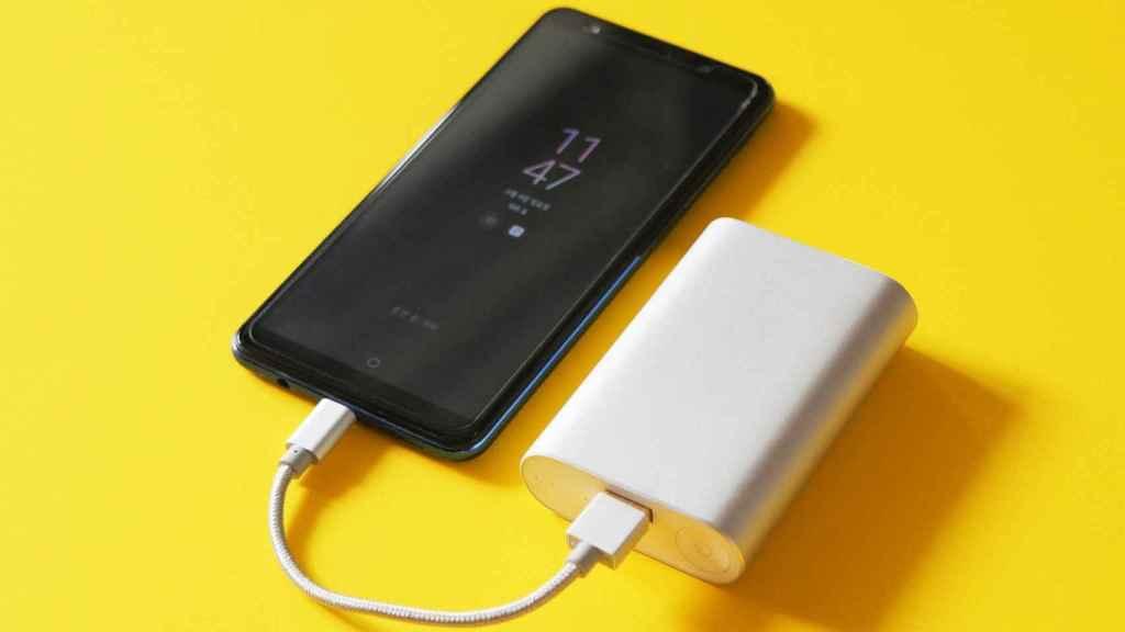 Un smartphone conectado a un cargador externo.