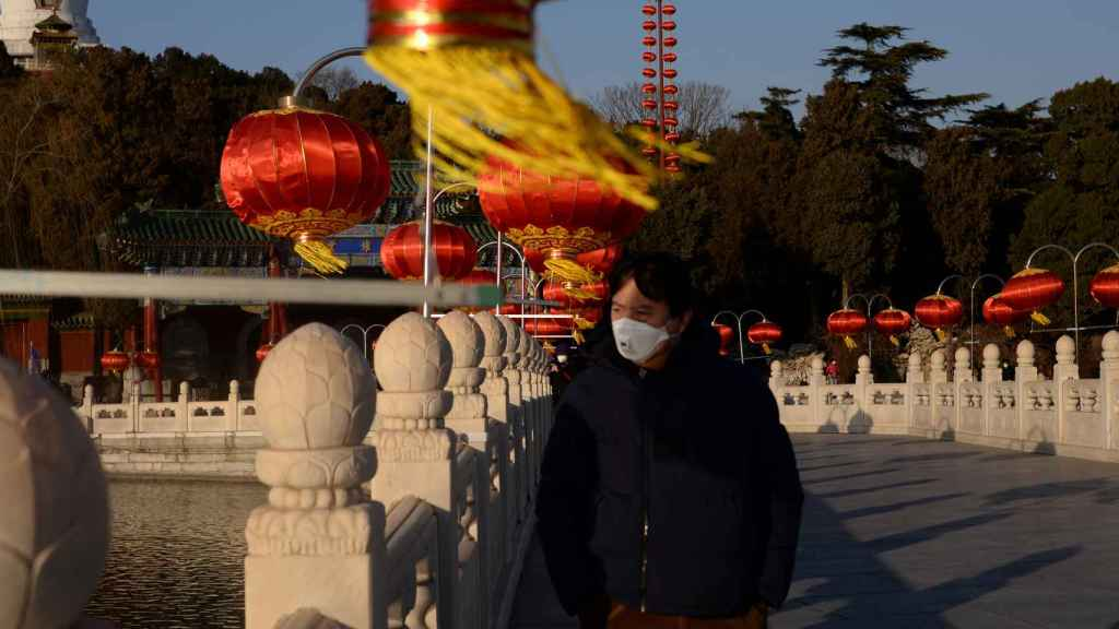 Un hombre pasea con mascarilla por Pekín.