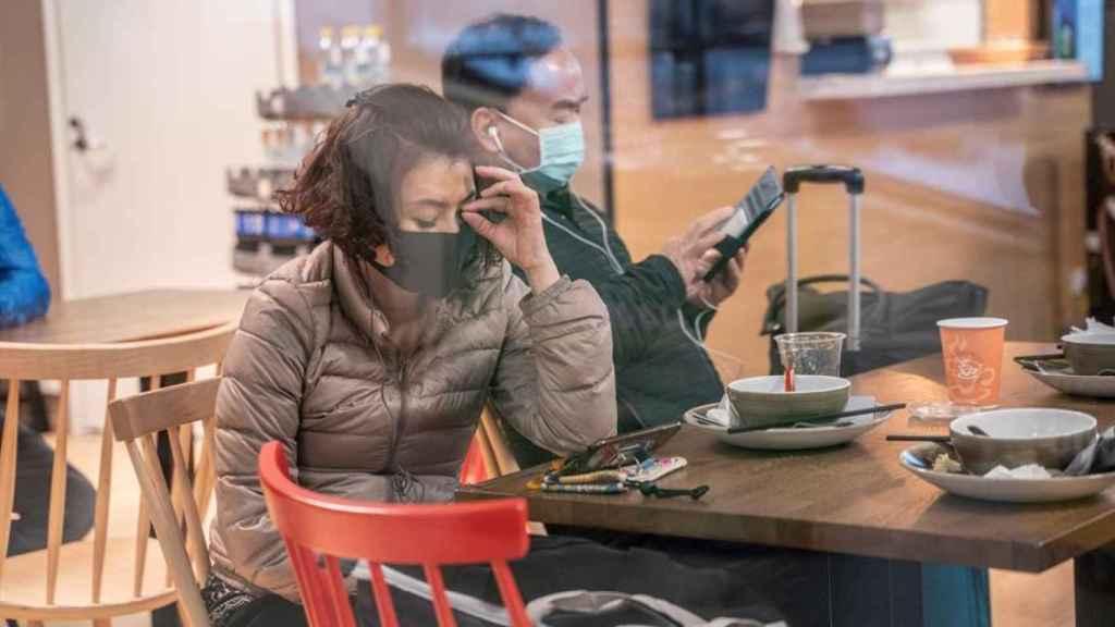Dos personas esperan en un aeropuerto con sus mascarillas.