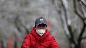 Una mujer monta en bicicleta usando una mascarilla en Pekín.