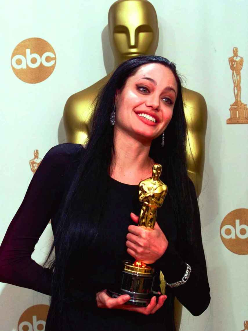 Angelina Jolie posing with the Oscar that she won in 2000.