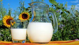 Un vaso de leche junto a una jarra.