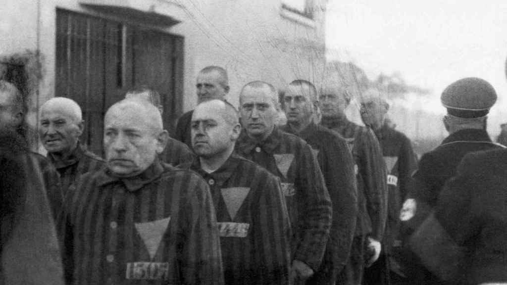 Prisioneros con triángulos rosas en sus uniformes marchan al aire libre bajo la vigilancia de los guardias de la SS en Sachsenhausen