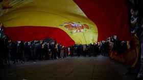 Una bandera de España de gran tamaño en una concentración.