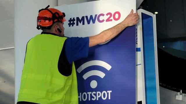 Un empleado coloca un cartel del Mobile de Barcelona