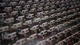 Trabajadores en Kunming, China, con mascarillas y ordenadores cubiertos
