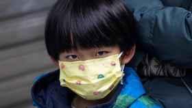 Un niño hace cola en la farmacia para comprarse una mascarilla en China.