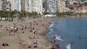 Varias personas toman el sol en la playa de La Malagueta en Málaga.
