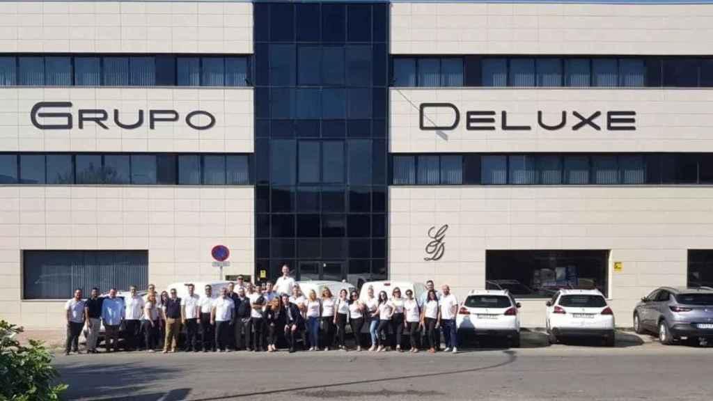 Los 42 empleados de Grupo Deluxe posan en la puerta de la empresa.