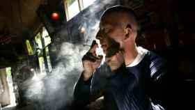 Un hombre fuma un  porro en un coffeeshop.
