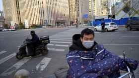Moteros con mascarilla en las calles de Pekín