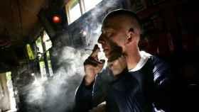 Un hombre fuma un cigarro de marihuana.
