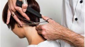 Un peluquero cortando el pelo de una mujer.