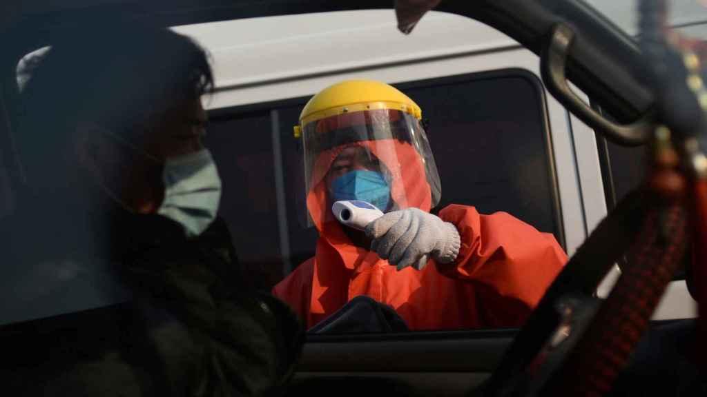 Sanitario tomando temperatura en Pekín