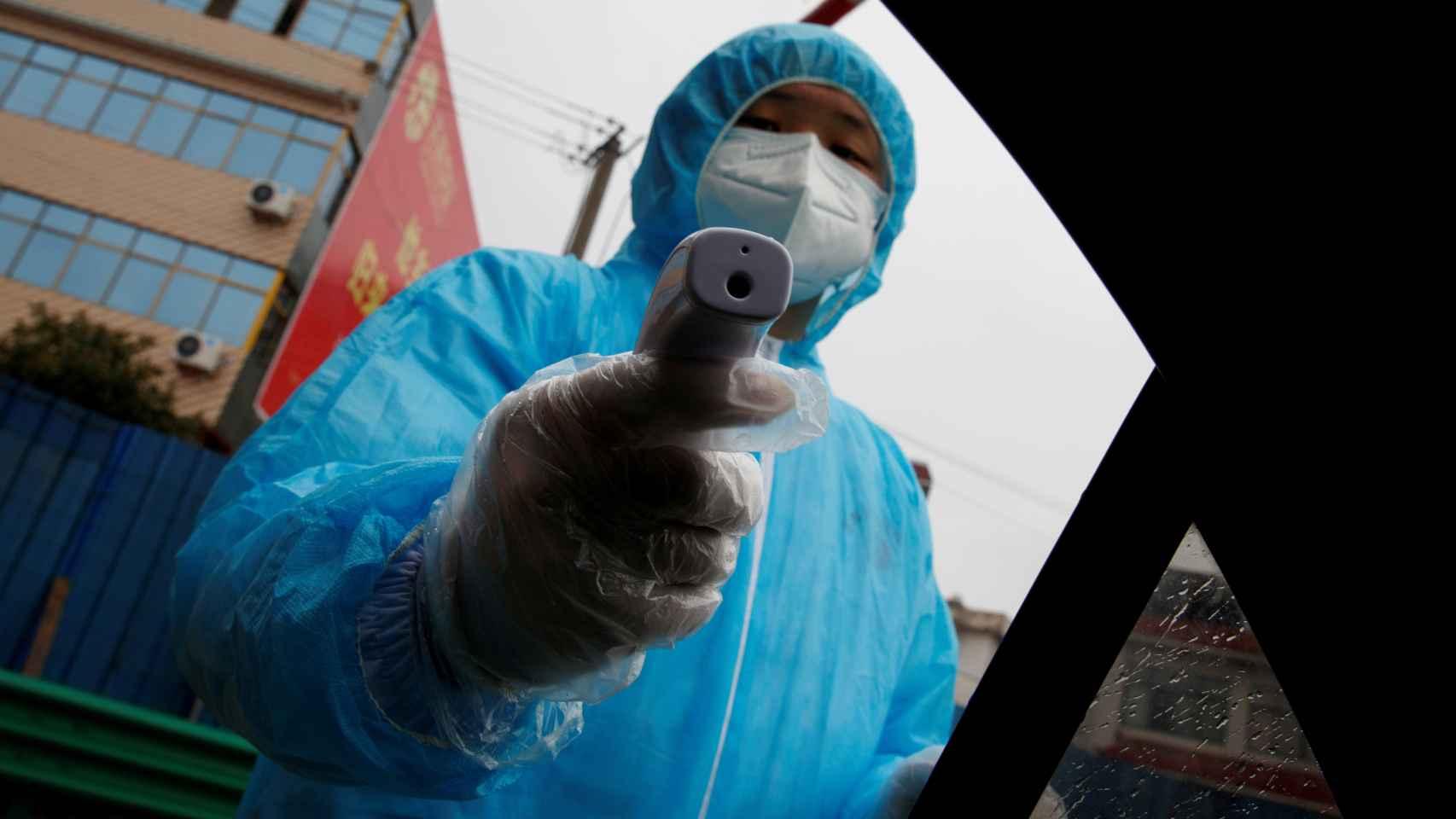 Sanitario tomando la temperatura con un termómetro infrarrojo